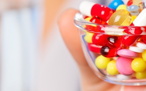 polypharmacy and the polypill - too many medications symbolized by a bowlful of pills