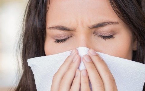 woman with allergies blowing her nose with a tissue
