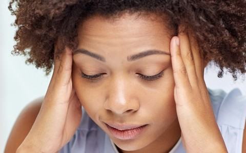 woman feeling stressed, how to lower the stress hormone cortisol