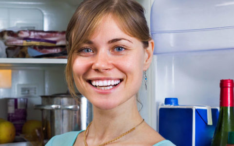 woman decluttering fridge to reduce stress